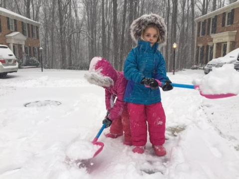 Young girls shoveling snow.